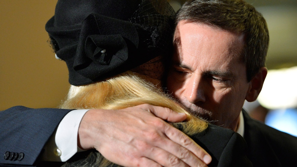 Ontario Premier Dalton McGuinty hugs widow Marni Alexander as he pays tribute to former Ontario lieutenant governor Lincoln Alexander as he lies in state at the Ontario Legislature at Queen's Park in Toronto on Sunday, Oct. 21, 2012. (Nathan Denette / THE CANADIAN PRESS)