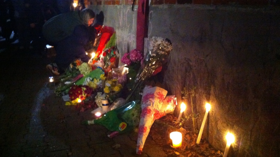 A woman places flowers by a memorial for stabbing victim Nighisti Semret in Toronto, Oct. 24, 2012. (Scott Lightfoot/ CTV Toronto)