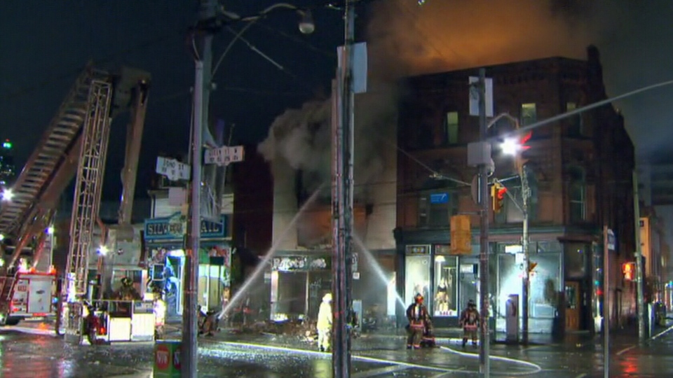 Toronto firefighters attend to the fire that engulfed a commercial building on Queen Street West on Tuesday, Oct. 30, 2012.