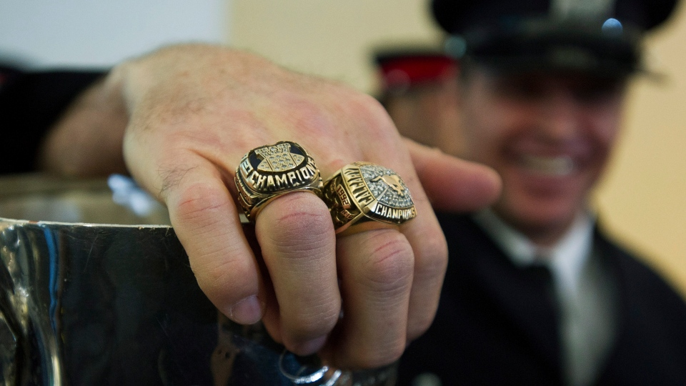 CFL alumni and firefighter Paul Clatney shows his CFL Grey Cup rings as the Grey Cup arrived at City Hall during a 100th year celebration that kicked off in Toronto on Friday, Nov. 16, 2012. (Nathan Denette / THE CANADIAN PRESS)