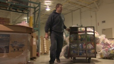 A Salvation Army warehouse worker handles toys
