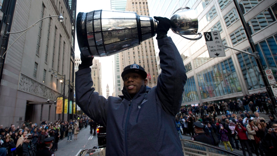 Toronto Argonauts Jordan Younger hoists the Grey Cup during the Grey Cup parade in Toronto, Tuesday, Nov. 27, 2012. ( Nathan Denette / THE CANADIAN PRESS)