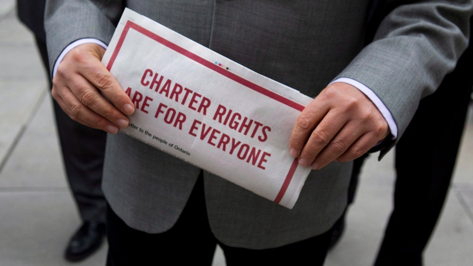 Fred Hahn, President of CUPE (Canadian Union of Public Employees) Ontario clutches an advertisement for Charter of Rights that appeared in newspapers as he walks towards the Ontario Superior Court of Justice with fellow union leaders, as they announce a legal challenge to Bill 115, in Toronto on Thursday October 11, 2012 . THE CANADIAN PRESS/Chris Young
