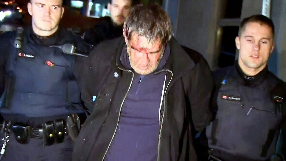 Toronto police officers transport Steven Paul Brunswick to hospital following his arrest early Thursday, Dec. 13, 2012.