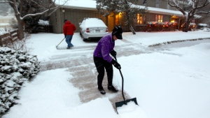 A woman and her husband shovel their walk