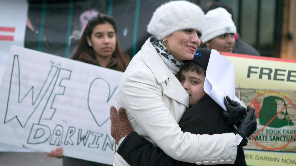 Yasmin Nakhuda (left) hugs her twelve year old son Misha outside an Animal Services office in Toronto on Wednesday, Dec. 19, 2012. (Chris Young / THE CANADIAN PRESS)