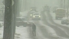 Cars drive as heavy snow falls in Windsor, Ont. on