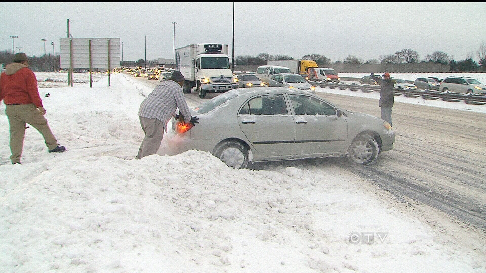 A group of snowplow drivers help free a car from a raised curb on Highway 401 in Toronto on Thursday, Dec. 27, 2012.