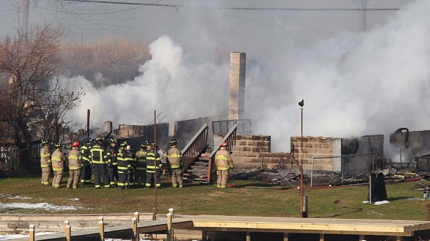 Firefighters gather around a burning house after they were let back into the area to battle the blaze in Webster, N.Y. on Monday Dec. 24, 2012. (Democrat & Chronicle, Jamie Germano)