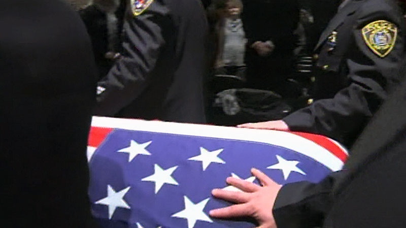 A coffin containing the body of police Lt. Michael Chiapperini, who was killed while volunteering as a firefighter, is carried by members of the police department in Webster, N.Y. on Sunday, Dec. 30, 2012.
