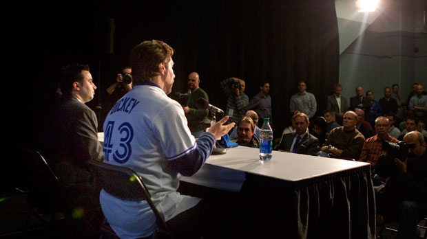 Pitcher R.A. Dickey sits with Toronto Blue Jays general manager Alex Anthopoulos (left) during a news conference in Toronto on Tuesday, Jan. 8, 2013 as the Jays introduce the newest addition to their roster. (The Canadian Press/Chris Young)