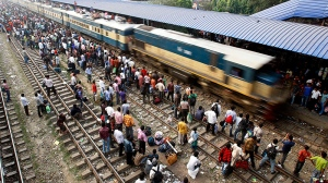 Bangladeshi passengers crowd a train station to travel home for Eid al-Adha, as an overloaded train arrives on the outskirts of Dhaka, Bangladesh, Saturday, Nov. 5, 2011. (AP / Pavel Rahman)