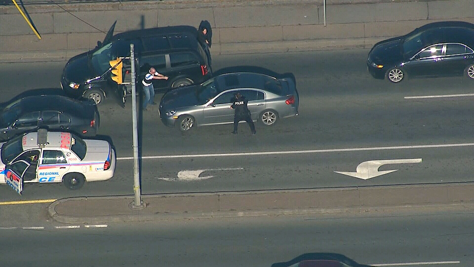 Police take aim at the driver of a car during an arrest near Sheridan Mall in North York on Wednesday, Jan. 16, 2013.