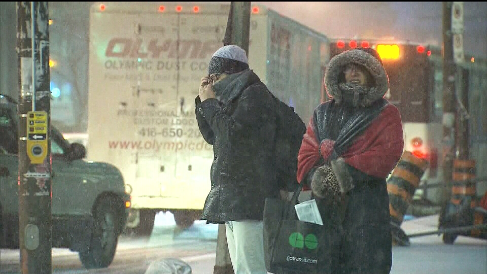 People adjust their winter clothing while waiting at an intersection in Toronto on Tuesday, Jan. 22, 2013.