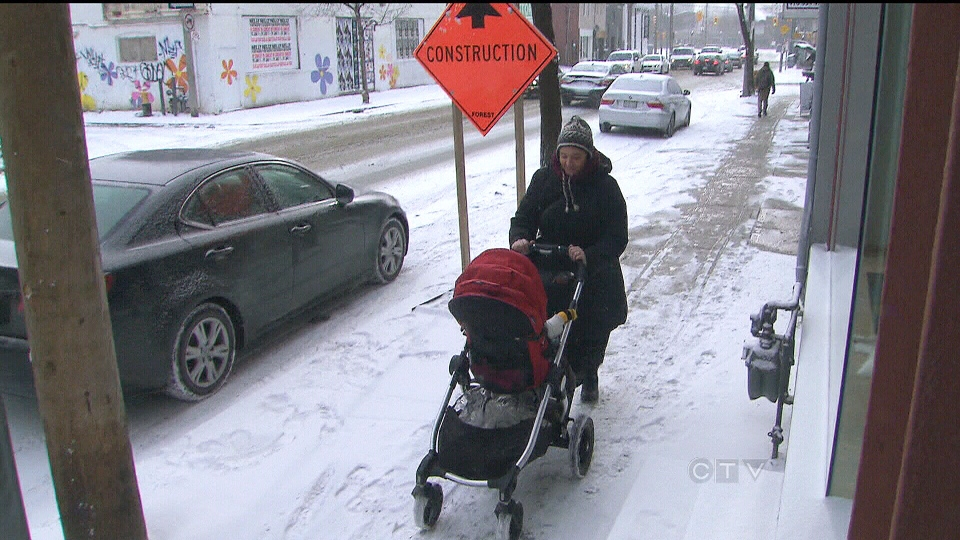 A TTC rider walk down the street pushing her baby in a stroller in Toronto on Tuesday, Jan. 22, 2013.