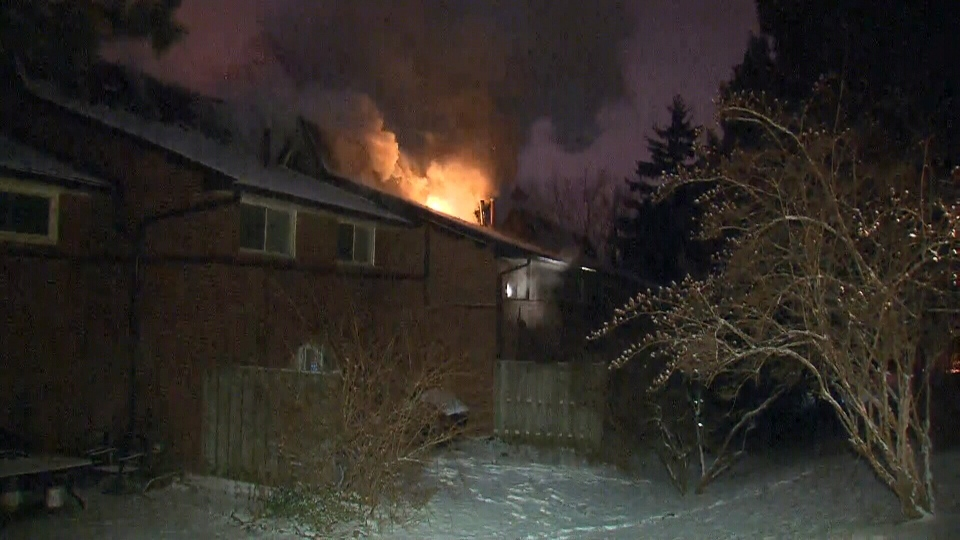 Flames are seen coming from the roof of a home on Esterbrooke Avenue early Jan.26, 2013 in Toronto. About 60 firefighters were called in to battle the blaze. (CTV Toronto / Tom Podolec)