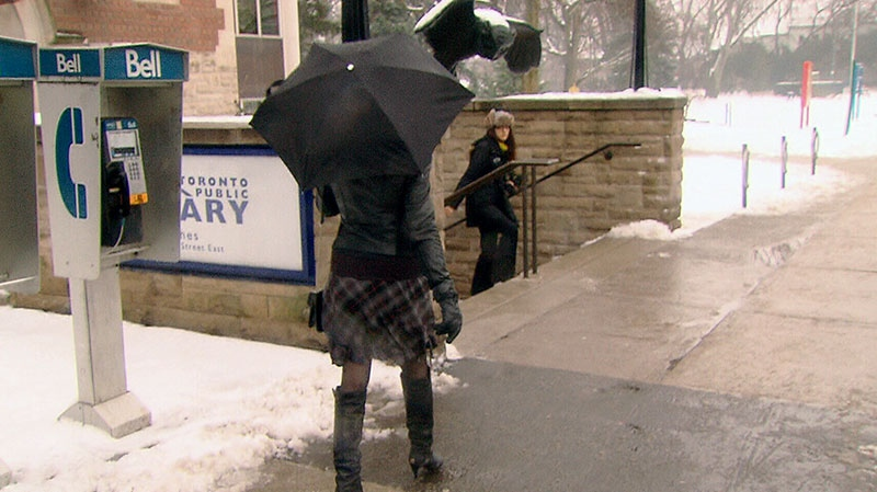 A woman walks on the sidewalk with an umbrella as freezing rain falls in Toronto, Monday, Jan. 28, 2013.