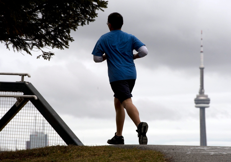 A runner in shorts rounds a bend as record-breaking temperatures hit in Toronto on Wednesday, Jan. 30, 2013. (Frank Gunn / THE CANADIAN PRESS)
