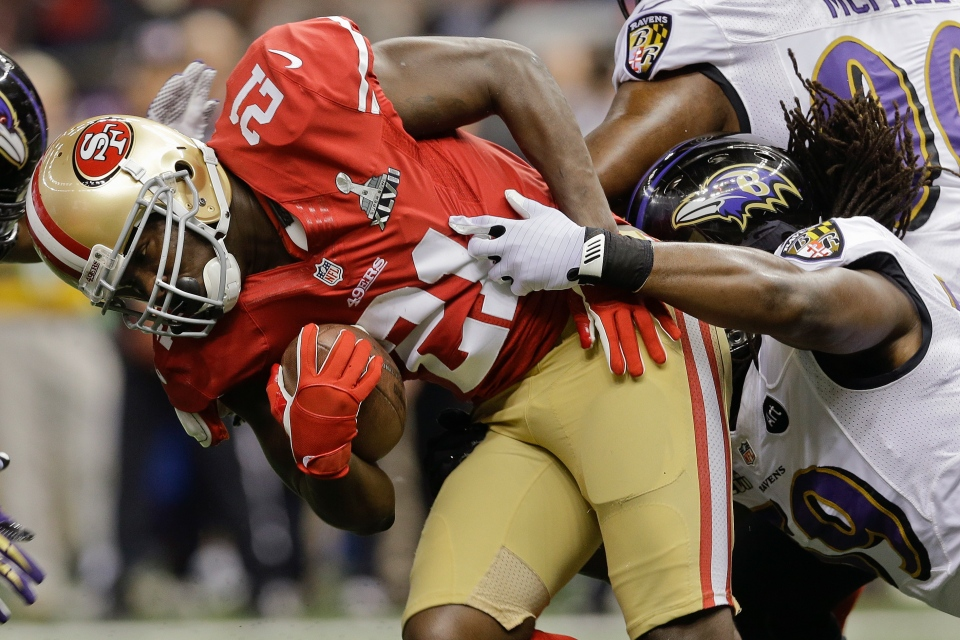 San Francisco 49ers running back Frank Gore (21) is tackled by Baltimore Ravens linebacker Dannell Ellerbe (59) in the first quarter of the NFL Super Bowl XLVII football game in New Orleans on Sunday, Feb. 3, 2013. (AP / Patrick Semansky)