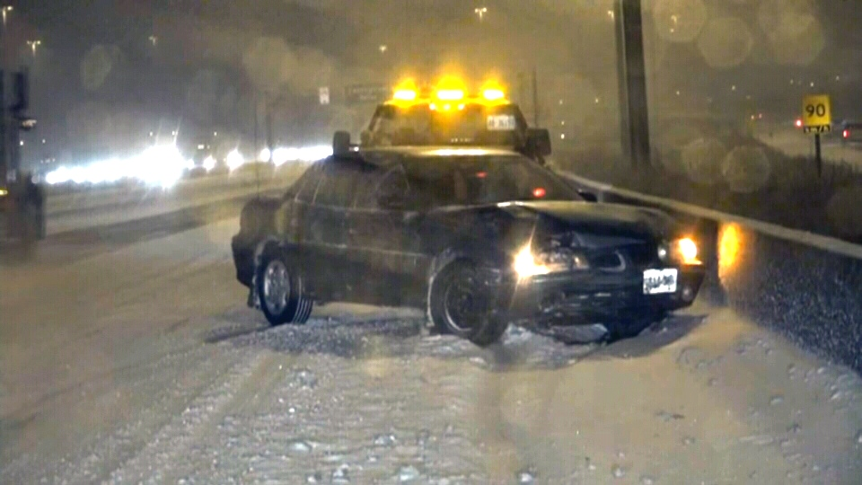 Emergency crews at the scene of a crash on Highway 401 in Toronto as a large storm hits the region, Friday, Feb. 8, 2013.