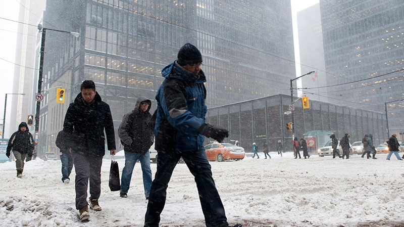 <br><br>Pedestrians cross a snow-covered street in downtown Toronto on Friday, Feb. 8, 2013. (Graeme Roy / THE CANADIAN PRESS)