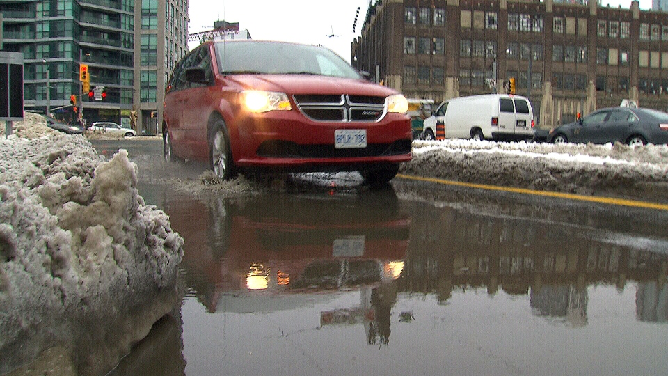 A motorist drives through a flooded street in Toronto on Monday, Feb. 11, 2013.