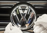 In this Nov. 9, 2012 file picture a worker fixes a sign at a Volkswagen Golf car during a press tour in Zwickau, central Germany. (AP Photo/Jens Meyer,File)