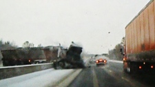 This screen grab, taken from amateur footage, shows a tractor trailer crashing through a guard rail on the Hwy 401, west of Toronto, on Friday, Jan. 21, 2011.