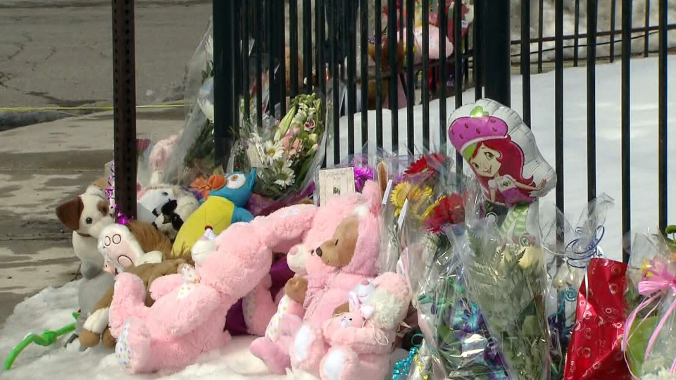 Toys, flowers and letters line the street corner in a makeshift vigil for a young girl who was fatally struck by a garbage truck the day before in Toronto, on Friday, March 8, 2013.
