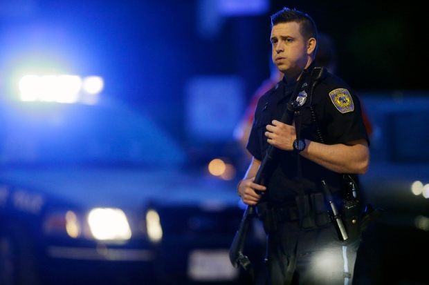 A massive manhunt for a suspect in the Boston Marathon has ended with a police capture, after parts of Massachusetts were shut down as officials went door-to-door hunting for the suspect. <br><br> A police officer stands guard at the scene as the search for suspect in the Boston Marathon bombings continues, Friday, April 19, 2013, in Watertown, Mass. (AP / Matt Rourke)