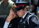 Gloria Kovach, left, the mother of fallen police officer Jennifer Kovach, is comforted by a Guelph police officer as they take part in a ceremony for the 14th annual Ontario police memorial ceremony at Queen's Park in Toronto on Sunday, May 5, 2013. (Nathan Denette / THE CANADIAN PRESS)