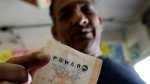 Joe Fajardo poses holding his Powerball lottery ticket after buying it at a store in the Barrio Logan neighborhood of San Diego, Saturday, May 18, 2013. (AP / Gregory Bull)