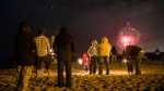 A family watches the Toronto Victoria Day fireworks on the beach on Monday, May 20, 2013. (Chris Young / THE CANADIAN PRESS)