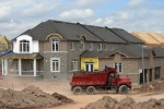 A dump truck gets set to dump clean fill at a new housing development in Oakville, Ont., in this 2011 file photo. (Richard Buchan/THE CANADIAN PRESS)
