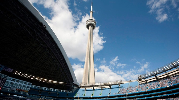 The CN Tower looms over the Toronto Blue Jays and Detroit Tigers as the Rogers Centre's roof is open for the first time in the 2011 MLB baseball season in Toronto Saturday, May 7, 2011. THE CANADIAN PRESS/Darren Calabrese