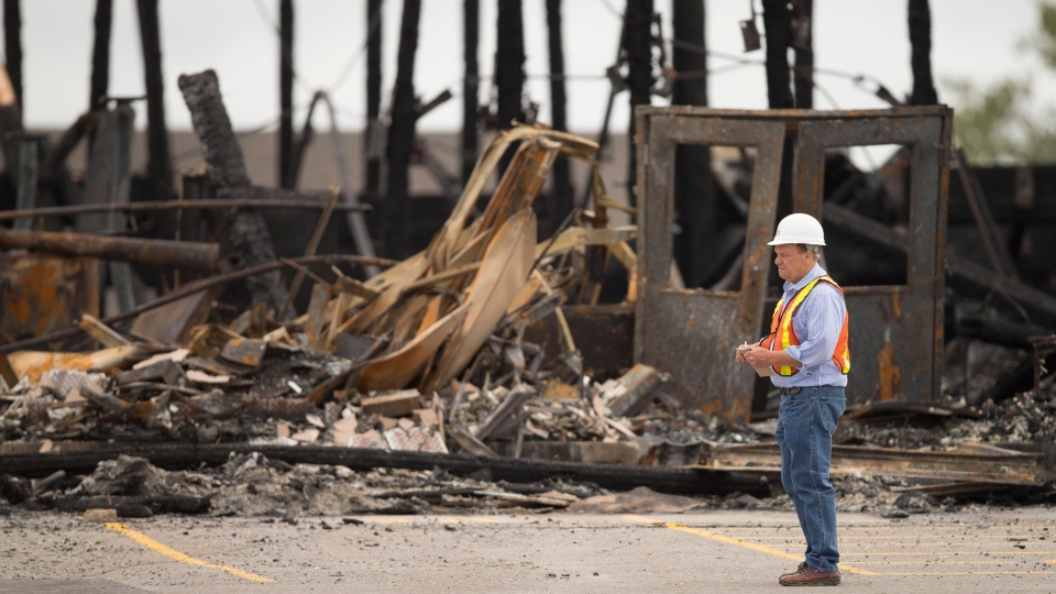 An investigator surveys the remains of the main building at the St. Jacobs Farmers Market in Waterloo, Ontario, Monday, Sept. 2, 2013. (Geoff Robins / THE CANADIAN PRESS)
