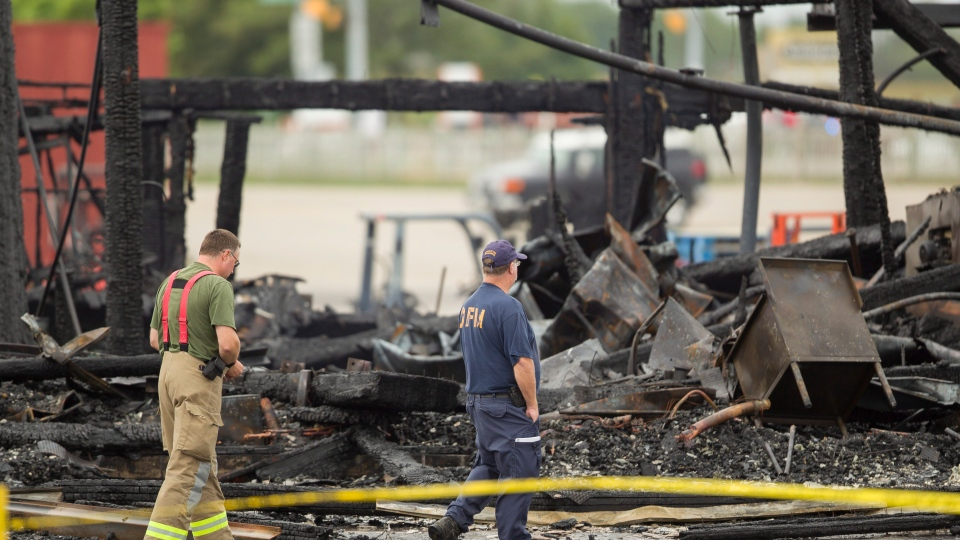 Investigators from the Ontario Fire Marshal's office survey the remains of the main building at the St. Jacobs Farmers Market in Waterloo, Ont., Monday, Sept. 2, 2013. (Geoff Robins / THE CANADIAN PRESS)