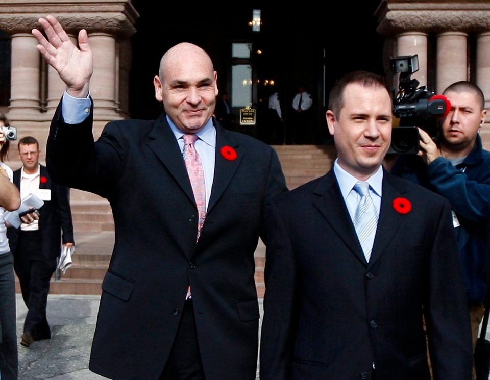 George Smitherman, left, and his husband Christopher Peloso, right, wave as they leave Queen's Park on Monday, Nov. 9, 2009 in Toronto. (Nathan Denette / THE CANADIAN PRESS)