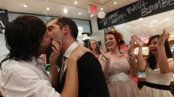 Lush Cosmetic employees Daniel Gervais, left, and David Casavant take part in a Kiss and Tell event in support of marriage equality as Amanda Halderman, second from right, and Perry Sun cheer them on, Saturday, June 18, 2011 in New York. The State Senate left the Capitol on Friday without tackling same-sex marriage and other key issues, but Gov. Andrew M. Cuomo insisted lawmakers are on track to take action before the end of the legislative session slated for Monday. (THE ASSOCIATED PRESS / Mary Altaffer)