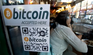 A Bitcoin ATM sticker is posted to the window of a coffee shop in downtown Vancouver on Monday, Oct. 28, 2013. (Jonathan Hayward / THE CANADIAN PRESS)
