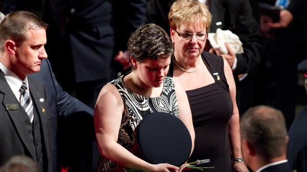 Melissa Styles clutches her husband's hat following the memorial service for York Regional Police Officer Constable Garrett Styles at the Ray Twinney Complex in Newmarket, Ont. on Tuesday, July 5, 2011. (Chris Young / THE CANADIAN PRESS)