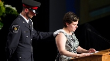 Melissa Styles is comforted by Police Officer Eric Loeffler as she reads a eulogy during the Remembrance Service for her husband, York Regional Police Officer Const. Garrett Styles, at the Ray Twinney Complex in Newmarket, Ont. on Tuesday, July 5, 2011. (Chris Young / THE CANADIAN PRESS)