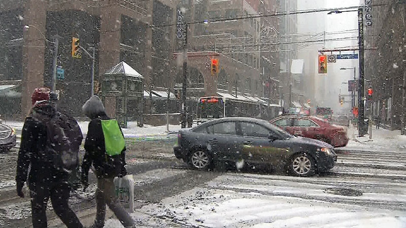 Pedestrians walk the streets of downtown as snow hammers down in Toronto on Saturday, Dec. 14, 2013.