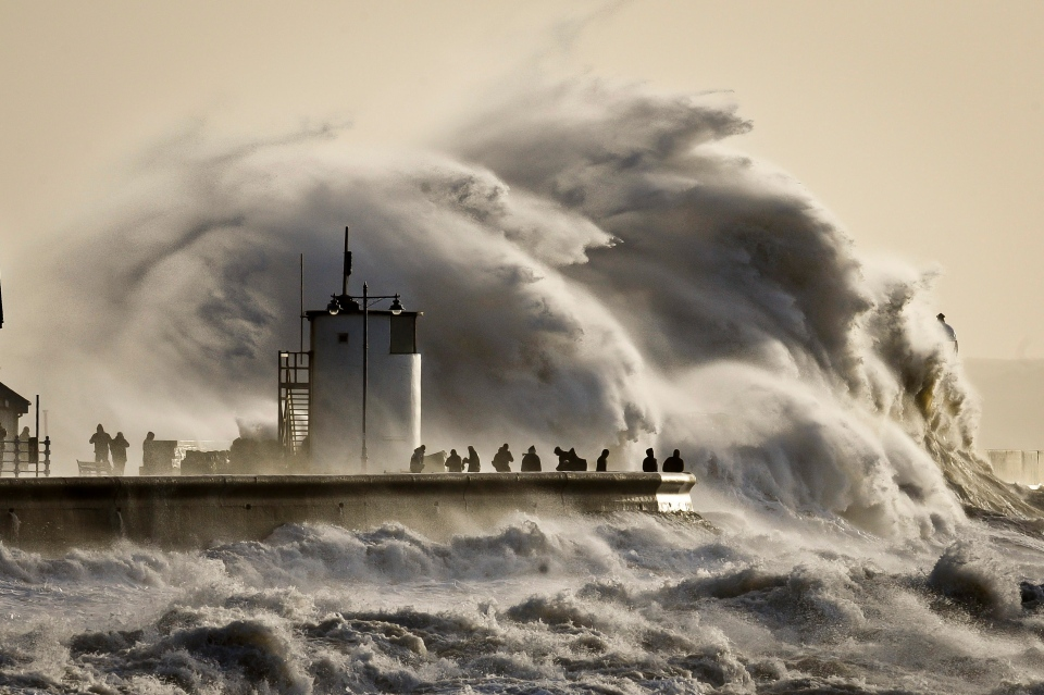 People watch and photograph enormous waves as they break, on Porthcawl harbour, South Wales, Monday, Jan. 6, 2014. (AP / PA, Ben Birchall)