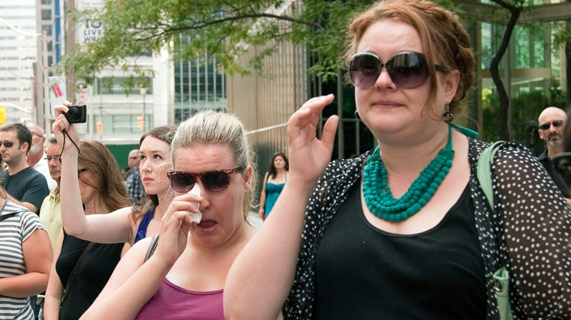 People cry as the funeral procession of NDP Leader Jack Layton leaves city hall in Toronto on Saturday, Aug. 27, 2011.