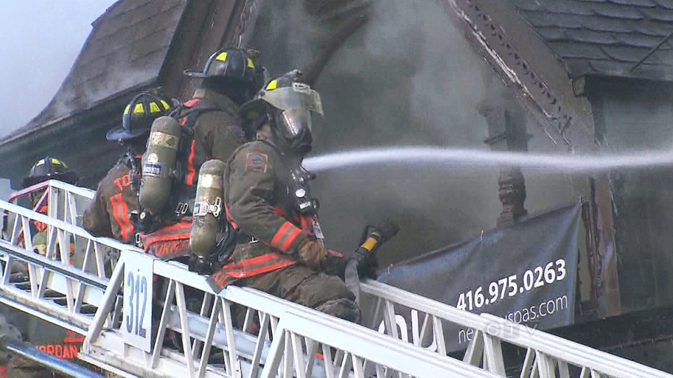 Toronto firefighters work to put out a blaze on Yorkville Avenue on Wednesday, Jan. 22, 2014.