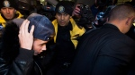 Canadian musician Justin Bieber is swarmed by media and police officers as he turns himself into city police in Toronto on Wednesday, January 29, 2014. (Nathan Denette / THE CANADIAN PRESS)