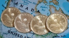 Loonies, are displayed on a map of North America, Thursday, Jan. 9, 2014. (Paul Chiasson / THE CANADIAN PRESS)