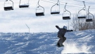A snowboarder gets some air in front of a silhouetted chairlift at Blue Mountain near Collingwood, Ont., on Thursday, Dec. 9, 2010. (Darren Calabrese / THE CANADIAN PRESS)