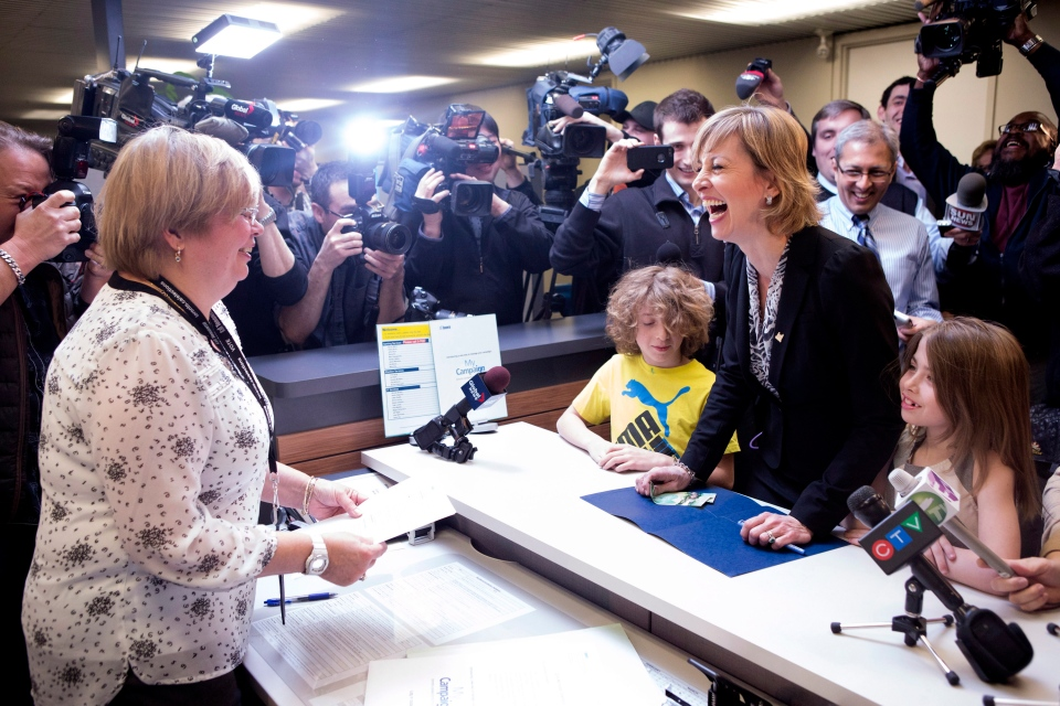 Coun. Karen Stintz (right), standing with her two children, Jackson and Hailey, prepares to hand over her nomination paper at Toronto's city hall on Monday, February 23, 2014. THE CANADIAN PRESS/Chris Young